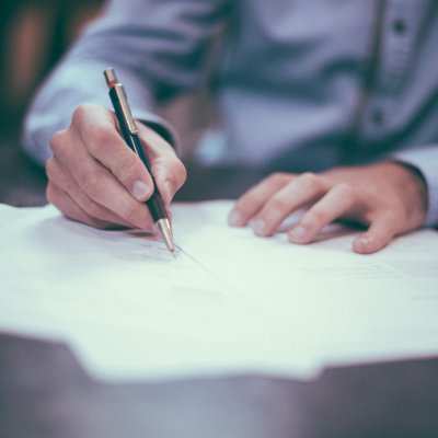 a person filling out a form with a pen